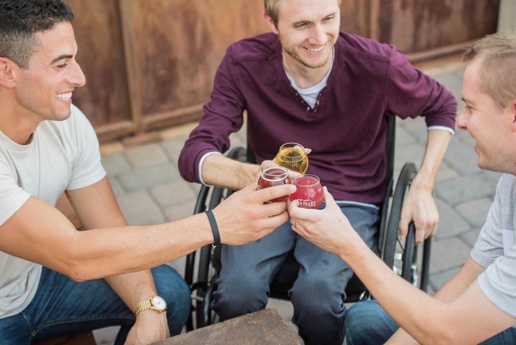 Rollstuhlfahrer stoßt mit Freunden an