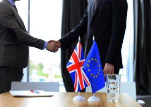 Händeschütteln hinter EU und GB Fahne